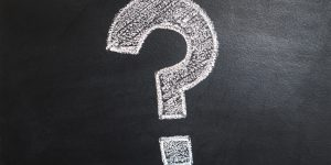 A black chalkboard has a bold question mark drawn in white chalk